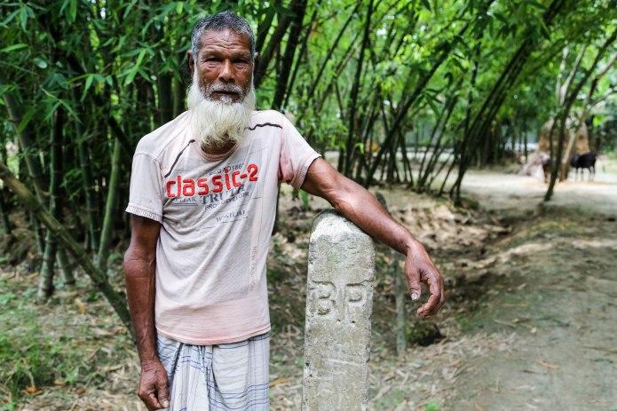 El septuagenario Ansar Ali posa su brazo sobre el poste que marca el comienzo del enclave indio de Bashkata, situado en el distrito bangladesí de Lalmonirhat. Ali es uno de los líderes de Bashkata.