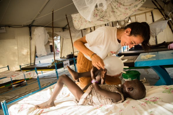MSF nurse Bárbara García and Nyamach play with a balloon made from a surgical glove in the inpatient ward of MSF's hospital in Ulang, in northeastern South Sudan.